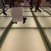 Photography of human feet. People walking on a glass white bridge in a shopping center. Concepts of shopping and lifestyles.